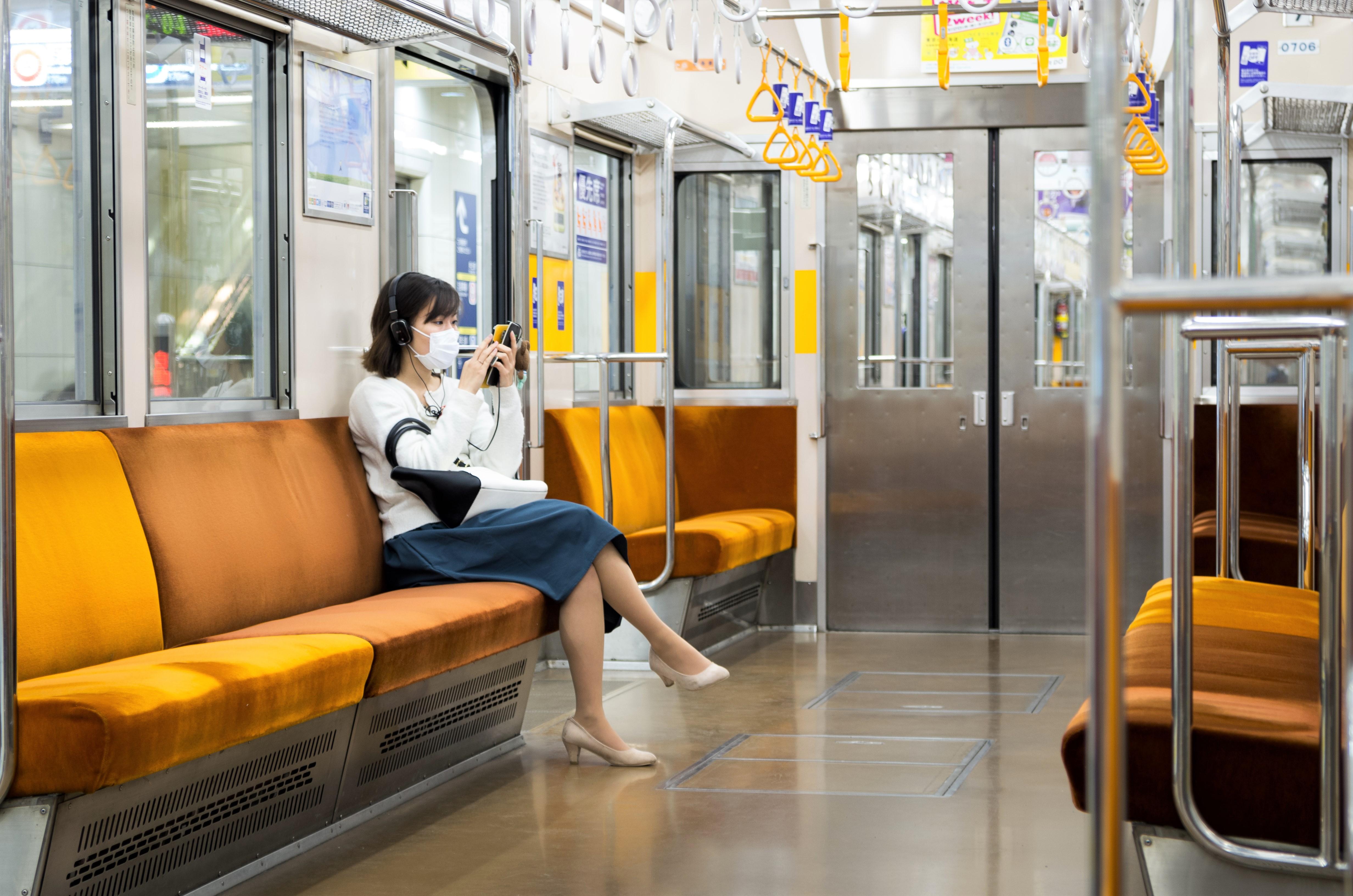 Eine Frau sitzt mit Handy und Mudschutz in der leeren U-Bahn in Tokio